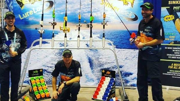 Darren Hodgson, centre, and friends with his display at the ICAST sportfishing convention in Orlando, Florida.