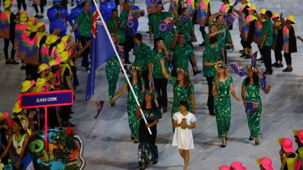 Flag bearer Ella Nicholas of the Cook Islands leads her team.