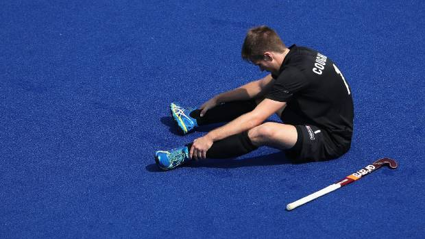 Black Sticks player James Coughlan sits dejected on the turf after New Zealand allowed a goal in the last minute.