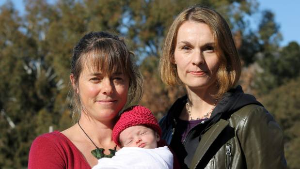 Lisa Johnstone, left, with her 11-day-old daughter, who is yet to be named, and midwife Deb Harvey.