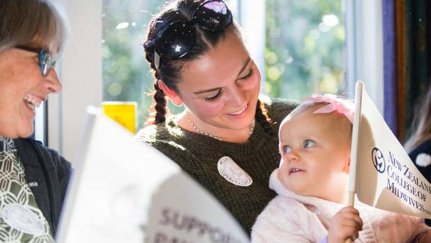 Midwife Jo Ryde entertains 14-month-old Charlie Francis, who sits on Reanna Montgomery's lap. Pay talks between the ...
