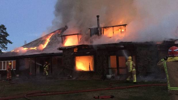 Firefighters battle a blaze at the Cluden Station homestead near Tarras on Tuesday.
