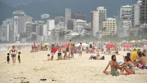 The Rio de Janeiro skyline rises behind Ipanema Beach.