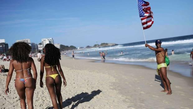 A man (R) waves US flag as women walk on Ipanema beach.