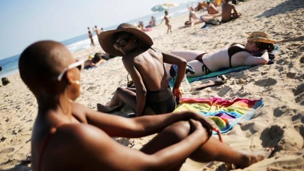 Tourists sunbathe on Ipanema beach.
