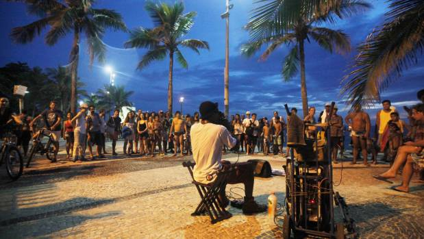 People watch a musician perform along Ipanema beach.