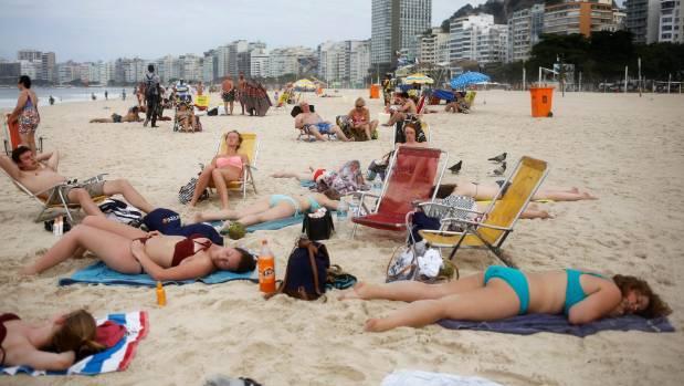 Tourists rest on Copacabana beach.
