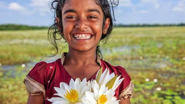 A little girl with lotus flowers in a lake near Sigiriya, Ceylon.
