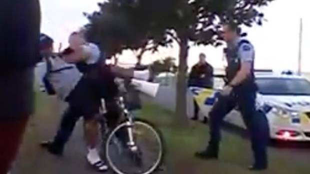 An Image taken from Cee La Tonga Taumoefolau's Facebook video showing a police officer pushing Matthew Heather, 13, from ...