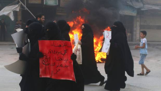 Women protest while burning tyres, which they said is used to create smoke cover from warplanes, in Aleppo, Syria on ...