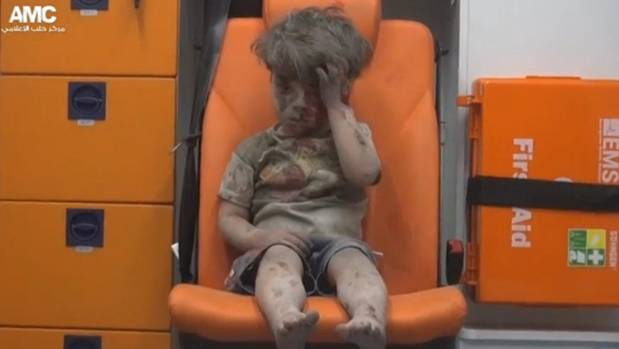 A boy sits in an ambulance after being injured in an airstrike in Aleppo, Syria, on August 18. His brother died.