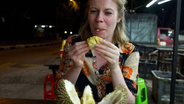 Travel reporter Siobhan Downes takes her first bite of durian.