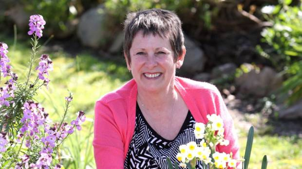 Christine Squier in her garden with spring flowers.