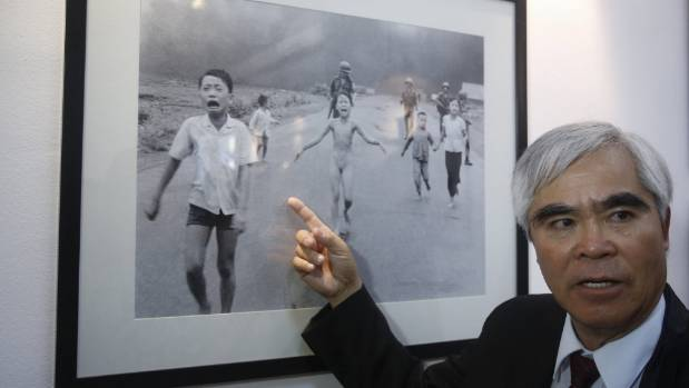 """Vietnam War photographer Nick Ut speaks with media next to his iconic """"Napalm Girl"""" photograph during a press event."""