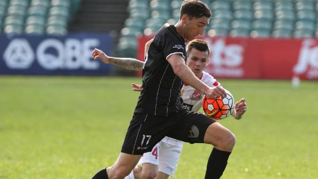 Waitakere's Jake Butler controls the ball under pressure from Birkenhead's Sam Burfoot.