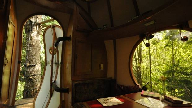 The Eryn sphere's interior with views of the forest through the doorway, skylight, and table-side window.