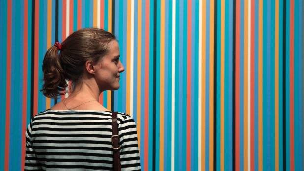 "A visitor poses with artist Bridget Riley's artwork ""Dauphin"" at a London exhibition in 2014."