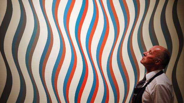 A Sotheby's employee stands in front of Bridget Riley's 'Image I Revised White' painting in 2013.