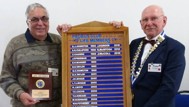 Rebus Club of Hibiscus Coast president Peter Odendaal awards John McColl with a Life Membership Award at a mid-year ...