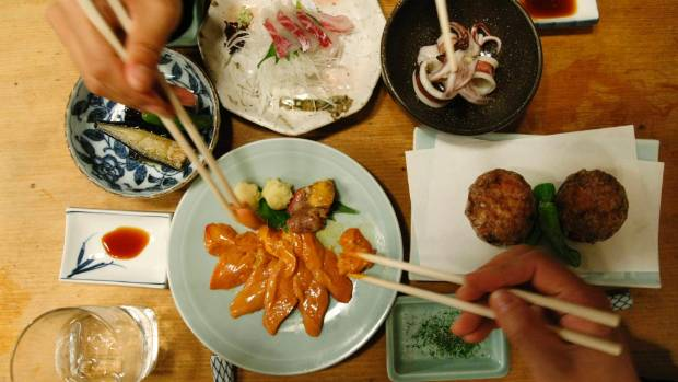 "People share dishes at a traditional Japanese ""Izakaya"" pub named Saiki in Tokyo."