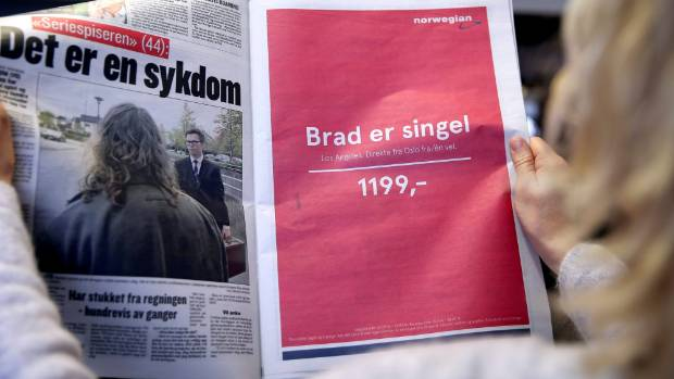 """A woman holds a newspaper with an advert for Norwegian Air Shuttle in Oslo. Advert reads: """"Brad is single. Los Angeles. ..."""