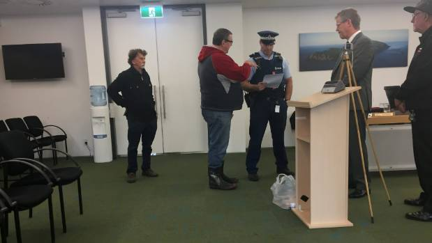 Public speaker Chris Walker pleads his case to a police officer called to eject him from the Kapiti Coast District ...