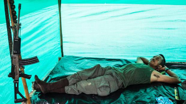 A FARC guerilla fighter from the southern bloc rests in his base camp in the llanos del yari, during the 10th conference ...