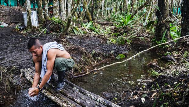 A FARC guerilla fighter from the southern bloc washes himself in the base camp in the llanos del yari.