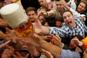 Visitors reach for the one of the first mugs of beer during the opening day of the 183rd Oktoberfest in Munich.