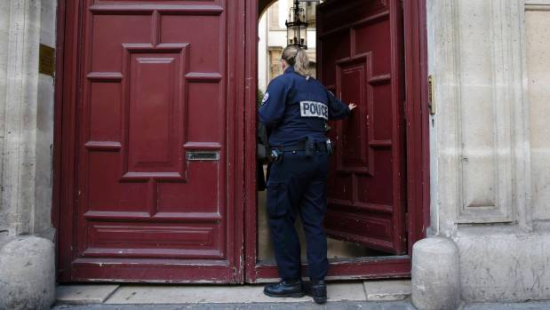 A police officer stands guard at the entrance of a luxury residence on the Rue Tronchet in central Paris where masked ...
