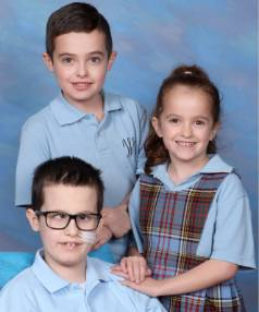 Caleb, with siblings Noah and Brooke, has missed school this year but was invited to be a part of photos to give him ...