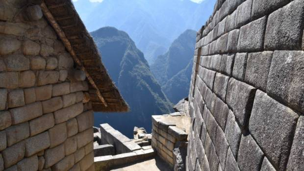 Stone walls look over the surrounding mountains at Machu Picchu.