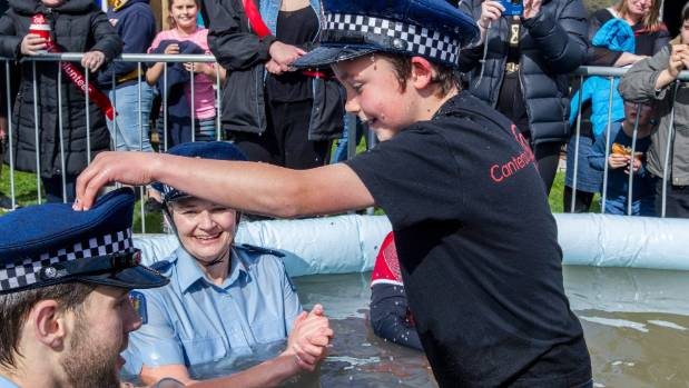 Wearing a borrowed police hat, Ashton Ball, 8, who has a heart condition, braved the icy water to dunk Constable Liam Wright.