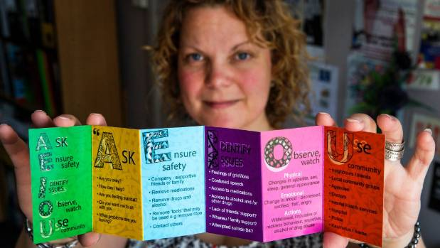 Registered psychologist Alicia Moxon with a pamphlet on suicide risk factors and what to do and where to get help.