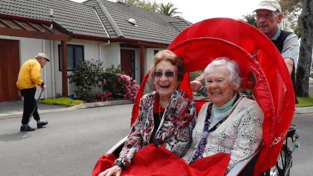 Pilot Trevor Higgs cycles Beryl White, left and Norma Best around Oakwoods Retirement Village in Richmond. Arvida which ...