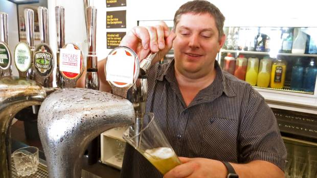 """Rick Keehan serving his recently-brewed """"Escape the Boss"""" lager at Ploughman's restaurant in Rainbow Point."""