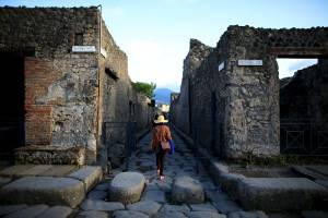 A tourist walks along an ancient Roman cobbled street at the UNESCO World Heritage site of Pompeii.