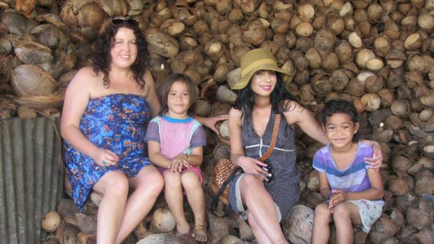 Members of The Body Shop team, Nicola Robinson and Rosie Rye, at a coconut farm in Samoa with local children.