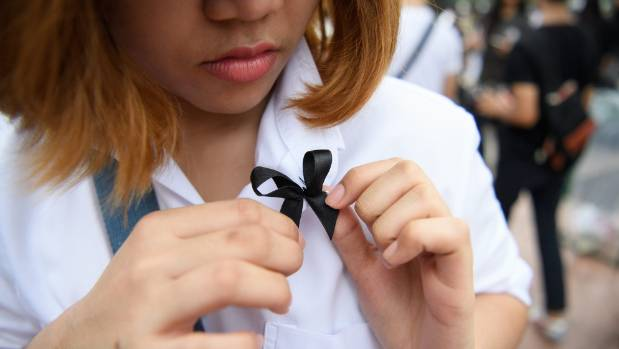 A Thai woman pins a black tribute ribbon to her blouse.