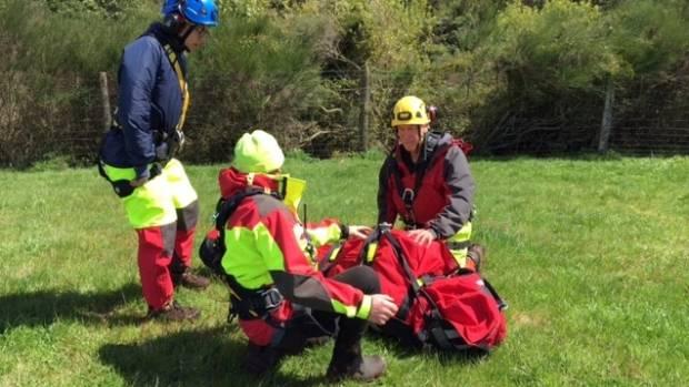 Rescuer prepare Louise Sisiaja for the lift into the rescue chopper.