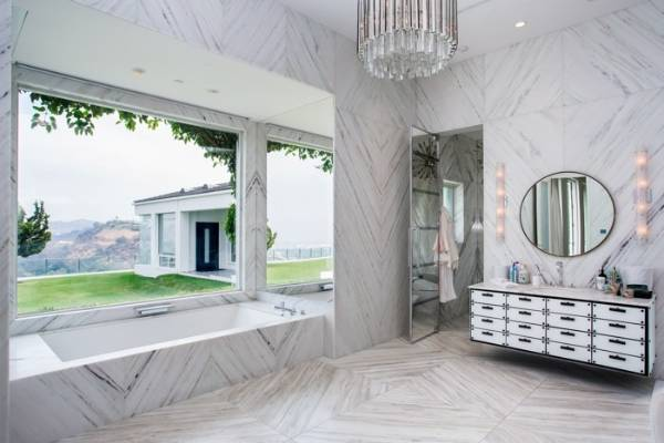 One of two master bathrooms, this one (hers) features matched marble panels on all surfaces.