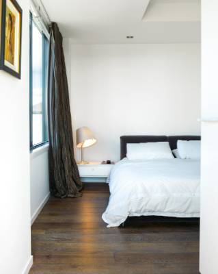 The simple white colour scheme extends into the master bedroom, where a Flos lamp from ECC casts a welcoming pool of light.