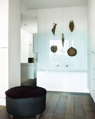 Five Len Castle pottery vessels stand out on white tiled walls in the master bathroom.