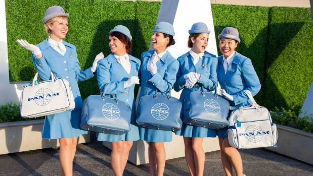 A bevy of stewardesses in their uniforms and travel cases gather outside and ceremoniously parade to the plane