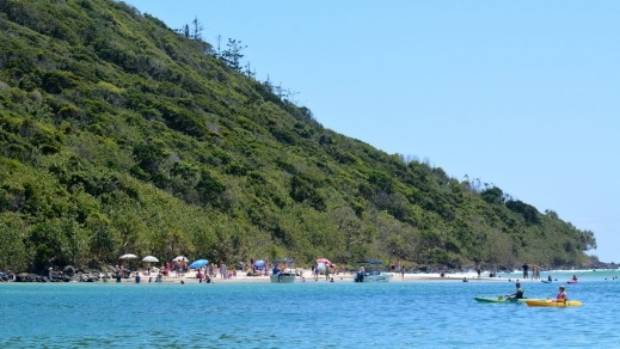 Visitors relax on the beach in Tallebudgera Creek.
