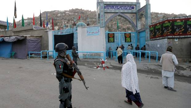 An Afghan policeman stands guard outside the Sakhi Shrine after an overnight attack in Kabul, Afghanistan.