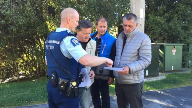 Queenstown Sergeant Chris Brooks hands out flyers for missing Australian tourist Robert Galdamez.