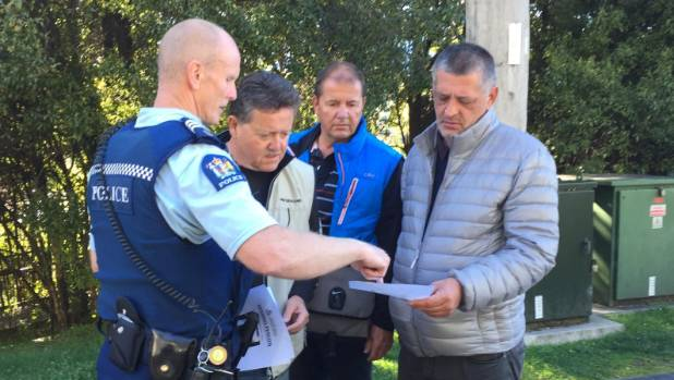 Queenstown Sergeant Chris Brooks hands out flyers in the search for missing Australian tourist Robert Galdamez.