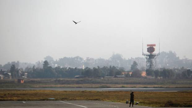 A member of the Nepalese army tries to shoot down an eagle at the Tribhuvan International Airport in Kathmandu.