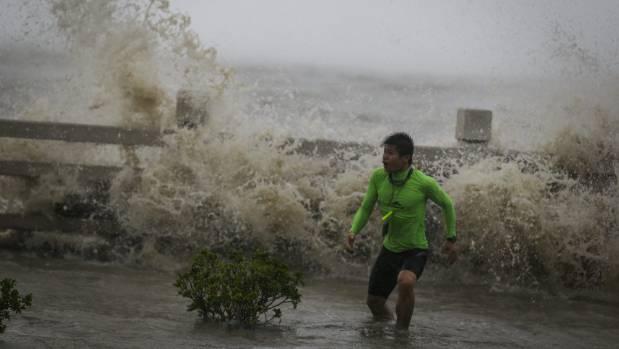 A man runs away from a wave at a beach as Typhoon Sarika lands in China.